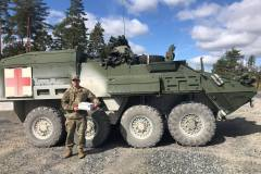 Military member in front of tank with care package